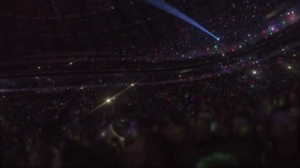 Efectos de iluminación asombrosos en arena con miles de personas disfrutando de la música de muestra — Vídeo de stock