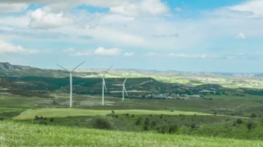 Amazing panorama of green field with spinning windmills, mountains on horizon — Stock Video