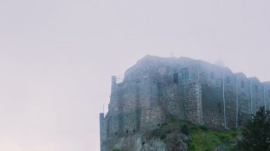 Old stone monastery standing on high hill hidden in fog. Ancient architecture — Stock Video