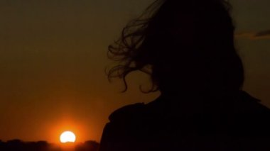 Dark silhouette of woman looking at sunset, wind waving her hair. Changes — Stock Video
