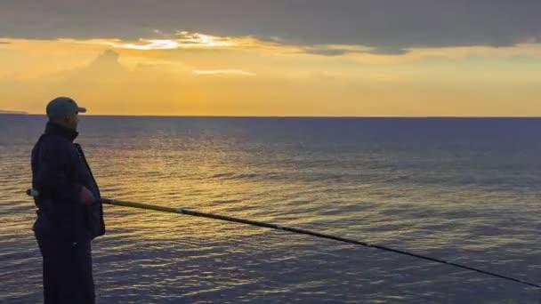 Hombre de pesca al amanecer, disfrutando de la afición, su tiempo de ocio con placer — Vídeo de stock