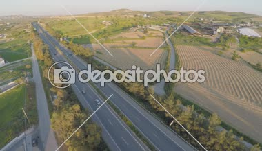 Aerial shot of many trees, harvested farming fields, green hills along highway — Video Stock