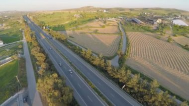 Aerial shot of many trees, harvested farming fields, green hills along highway — Vidéo