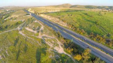 Fantastic aerial shot of beautiful landscape, green hills, busy traffic on road — Stock Video