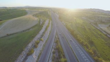 Vehicles moving on interstate highway. Beautiful sunset on horizon. Aerial shot — Stock Video