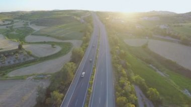 Busy traffic on motorway. Aerial shot of road, beautiful nature. Amazing sunset — Stock Video