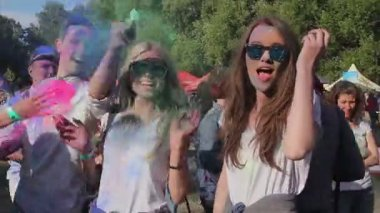 KYIV, UKRAINE -JUNE 11, 2015. Celebration of Holi Color Festival. Guys spraying colorful powder over pretty girls, happy friends hang out at event — Stock Video