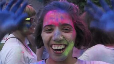 KYIV, UKRAINE -JUNE 11, 2015. Celebration of Holi Color Festival. Closeup of pretty girl covered in paint talking, winking at camera, happy crowd — Stock Video