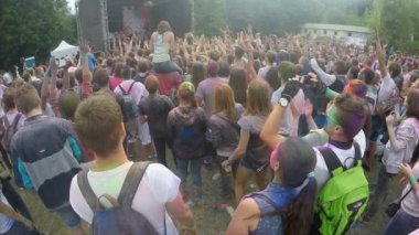Girl sitting on boyfriend's shoulders spraying colorful powder over happy crowd — Stock Video
