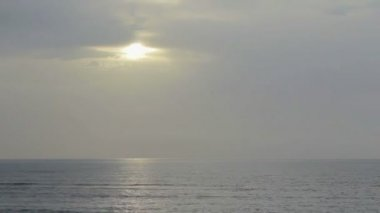 Sun hiding behind gray clouds in gloomy sky over endless sea surface. Timelapse — Stock Video