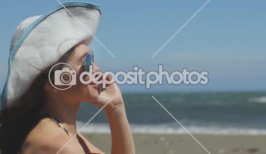 Excited young woman on beach talking emotionally on phone, waving hands, smiling — Stock Video
