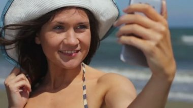 Happy young woman making selfie on seaside beach, taking picture on smartphone — Stock Video
