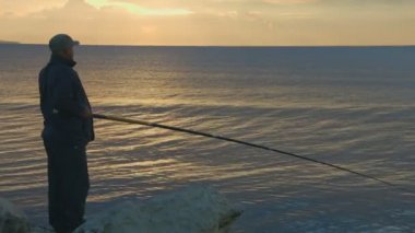 Elderly man fishing with rod from a rocky ocean shore, active rest, magic hour — Stock Video