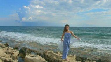 Happy beautiful woman standing on rocky sea beach, foamy waves crashing ashore — Stock Video