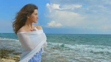 Lonely brunette wrapping herself in scarf, looking at ocean waves. Windy weather — Stock Video