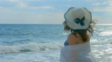 Woman wrapped in white scarf looking at beautiful ocean waves, early autumn — Stock Video