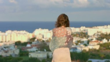 Sad woman wrapped in scarf looks at seaside town, amazing landscape, magic hour — ストックビデオ