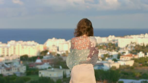 Sad woman wrapped in scarf looks at seaside town, amazing landscape, magic hour — Vídeo de stock