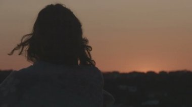 Lonely woman looking at burning sky at sunrise, sunset. Hair blowing in the wind — Stock Video