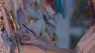 Closeup of woman tying a ribbon to the wishing tree. Traditions, symbol of luck — Stock Video