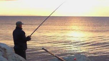 Man fishing at seaside, enjoying tranquil hobby on vacation, beautiful sunrise — Stock Video