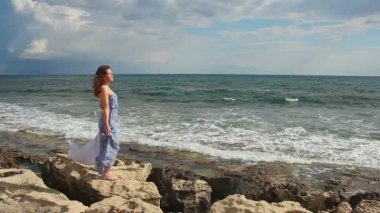 Woman in love standing on stones, stormy sea waves splashing, romantic mood — Stock Video