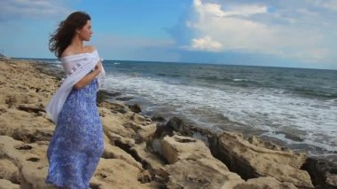 Sad lonely young woman looking at stormy sea, waves splashing, rocky shore, wind — Stock Video