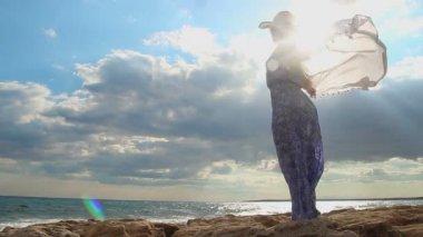 Silhouette of free woman in sunlight, beautiful seascape, sun hiding in clouds — Stock Video