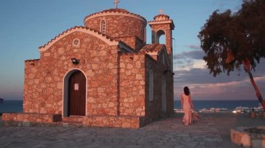 Beautiful Greek woman walking near old church, looking at amazing seascape — Stock Video