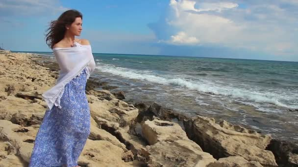 Hermosa hembra joven envuelta en la bufanda en la rocosa orilla del mar, pensando en futuro — Vídeo de stock