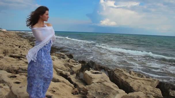 Bastante joven en permanente estado de ánimo romántico junto a la mar, mirando las olas tempestuosas — Vídeo de stock