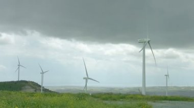 Wind turbines spinning in green field under gray stormy sky, bad rainy weather — Stock Video