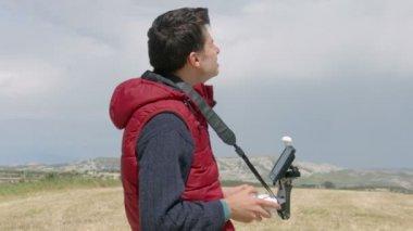 Man controlling quadrocopter flight, professional cameraman filming aerial video — Stock Video