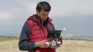 Professional cameraman controlling drone flight, watching display, filming video — Stock Video