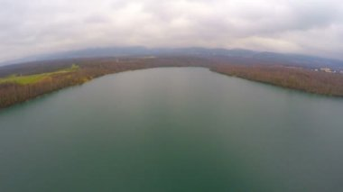 Aerial shot of autumn landscape, wide still river, gray clouds in sky on horizon — Stock Video