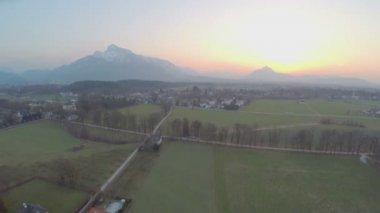 Beautiful mountains hiding sun on horizon, green farming fields, amazing sunrise — Stock Video