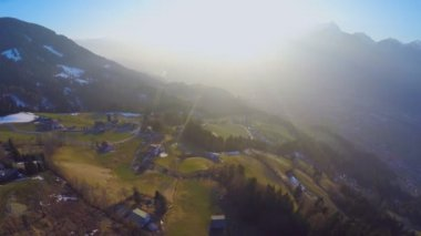 Aerial shot of small farming village on green hill of mountain in rays of sunset — Stock Video