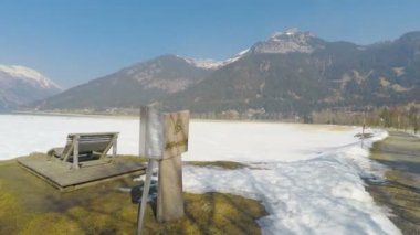 Stone bench at national park in Austrian Alps, snow melting, sunny spring day — Stock Video