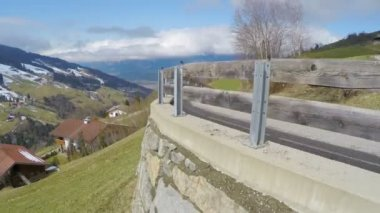 Serpentine road in high mountains, cloudy sky over green slopes, Alpine village — Stock Video