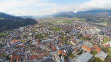 Aerial panorama of Swarovski factory hometown, majestic mountain range around — Stock Video