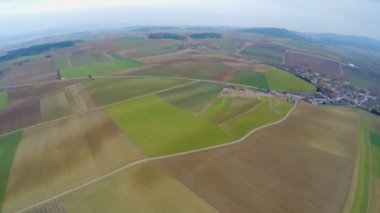 Flying over green cultivated fields in cloudy weather. Amazing  landscape — Stockvideo