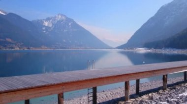 Horizontal pan of wooden pier near beautiful lake, mountains covered with snow — Stock Video