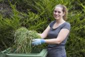 Girl with grass near green bin — Stock Photo