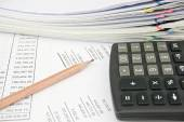 Calculator and pencil on statement with balance sheet — Stock Photo
