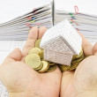 Man holding paper house on pile gold coins — Stock Photo #53745291