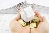 Man holding house on pile gold coins over finance account — Stock Photo