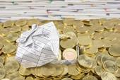 Gift box in heap of gold coins — Stock Photo