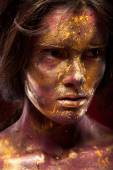 Girl with gold paint on face — Stock Photo
