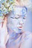 Woman with face art and flowers — Stock Photo