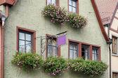 Flower baskets beneath windows in Rothenburg — Stock Photo